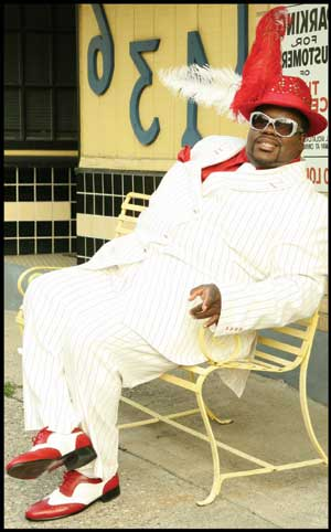Bigg Robb dressed in a white suite
